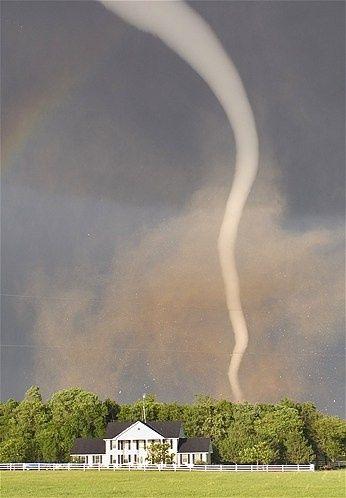 Kansas tornado: A ghostly white tornado spins near a house in Kansas.
