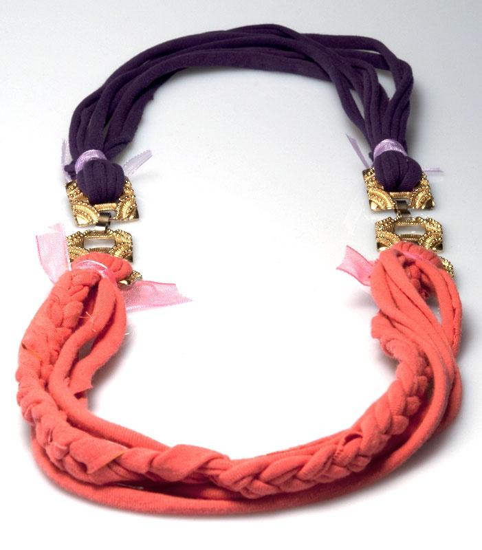 """""""Arianna"""" è una ricreazione bicolore ricavata da due T-shirt. Le strisce di cotone rosa si intrecciano e si congiungono con quelle viola attraverso due anelli quadrati appartenuti ad un vecchio gioiello. Le collane in stoffa sono una ricca collaezione di Rijoux."""