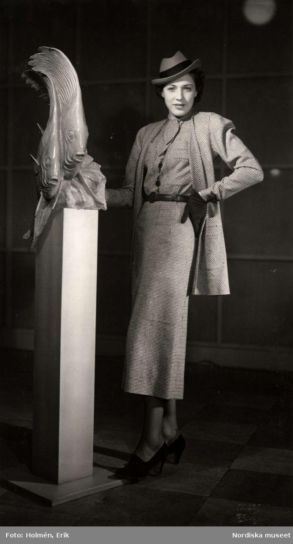 En kvinnlig modell poserar iklädd dräkt brevid en skulptur i föreställande av två fiskar. Kjolen är vadlång, blusen har knytband, jackan är av ledig modell. Fotograf: Erik Holmén, 1937