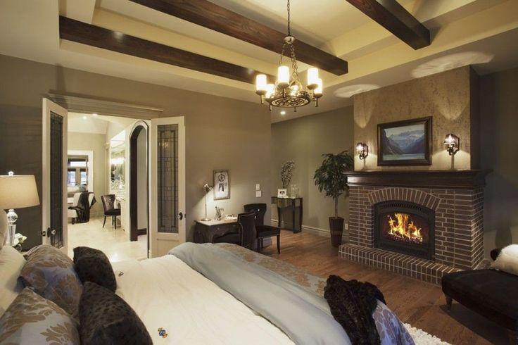 Dieses Master-Schlafzimmer weiße doppelte Tablett Decke Funktionen dunkle Decke Balken und einem traditionellen Gusseisen Kronleuchter.