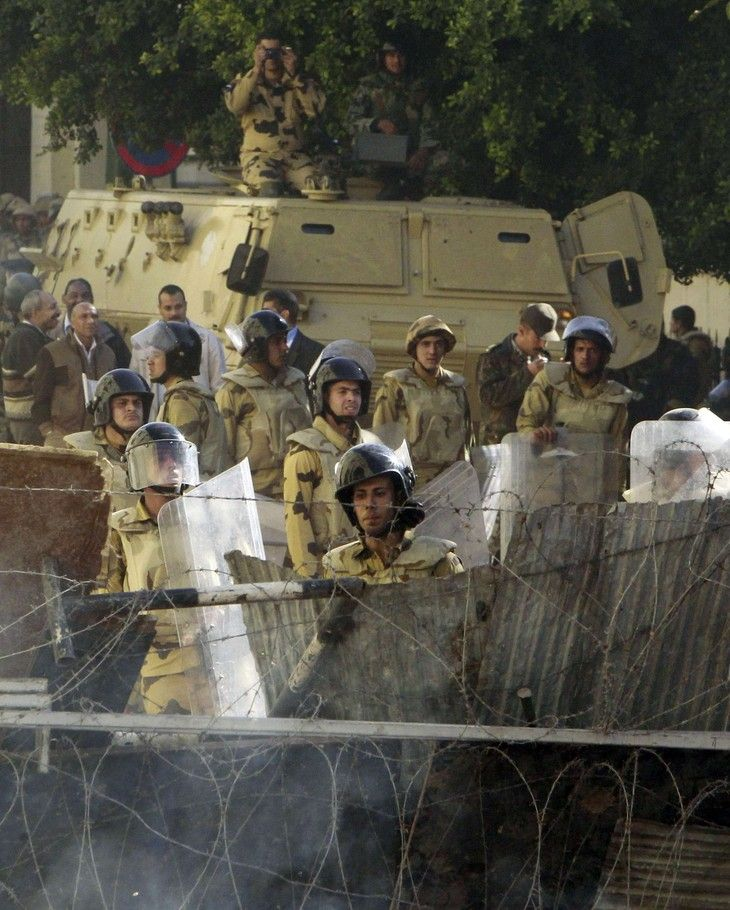 Army soldiers stand guard during clashes with protesters at cabinet offices near Tahrir Square in Cairo