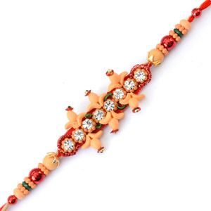 Giftblooms.com brings you this beautiful Rakhi which you can send to your brother in India on this joyous celebration. This Rakhi has two two unique designs parallel to each other, studded with sparkling stones in between. Moreover, this entire design rests on a red colored base. At both ends of this Rakhi there are red, cream and colorful beads which gives it a very traditional look.