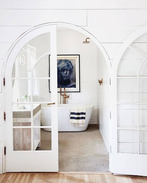 all white bathroom with freestanding tub and double french doors for the grand entrance