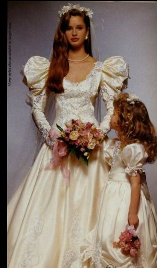 Late 1980s wedding gown and flower girl dress. this actually has a tasteful headpiece and bouquet, is a nice colour and has a lovely flowergirl outfit. Still very 80's with the puffy sleeves. Possible for our bride.