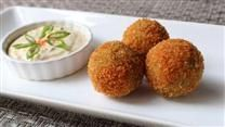 A flavorful sausage and sauerkraut mixture is breaded and baked into delicious appetizer balls.