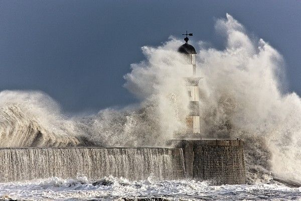 Waves Crashing Up Against A Lighthouse Print by John Short