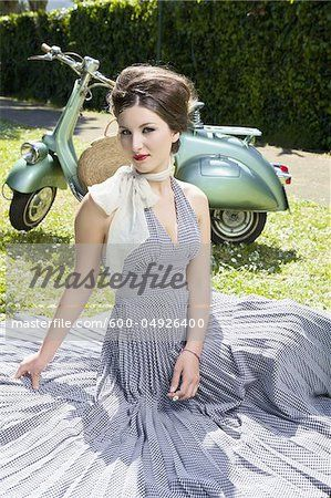 Stock photo of Woman Sitting on Grass with Scooter, Rome, Italy; Premium Royalty-Free, 600-04926400 © Siephoto / Masterfile. All rights reserved.