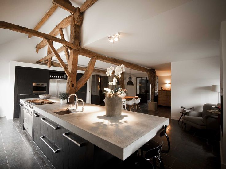 kitchen with antique oak beams, concrete workplate, fireplace and diningtable