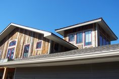 Barn Siding Ideas | Barn siding accents the dormer and tower of a lakeside home.