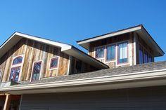 Barn Siding Ideas | Barn siding accents the dormer and tower of a lakeside home.