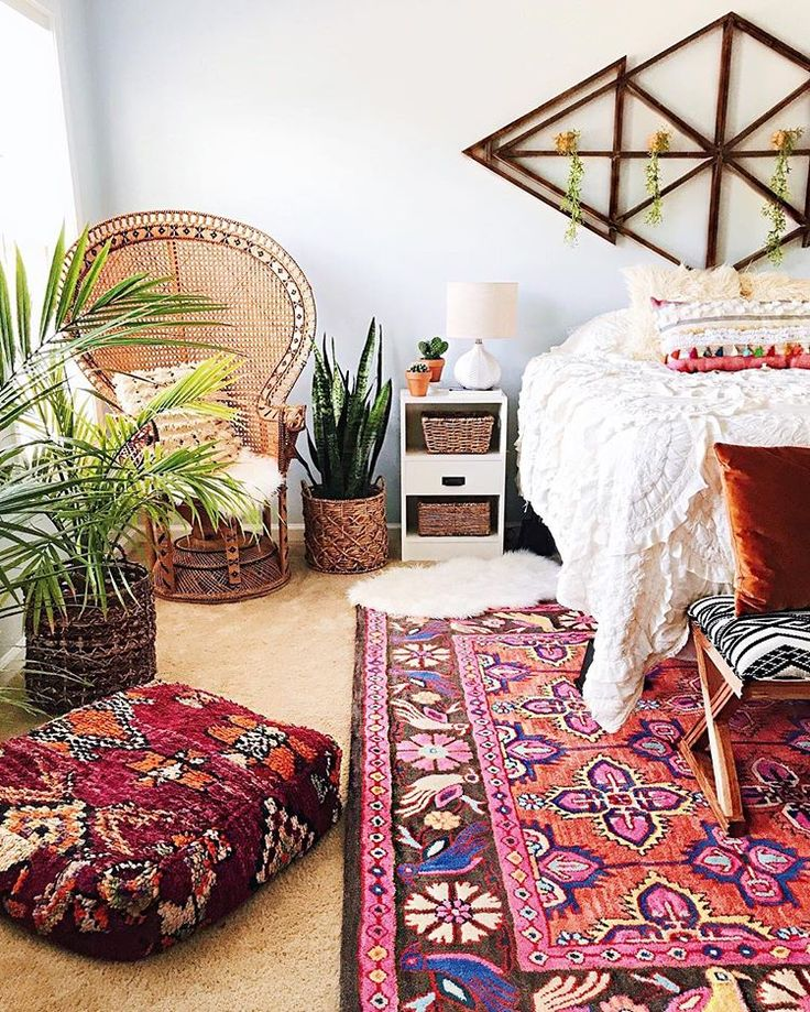 Colorful rug over carpet in bold bohemian bedroom by