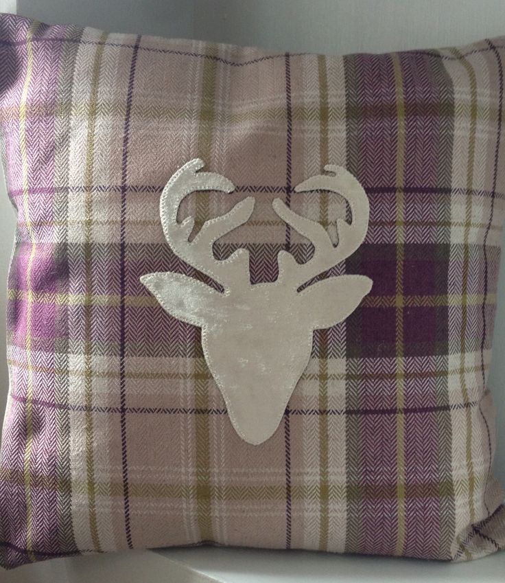 I make these stag appliquéd cushion covers, this is a lovely purple check tweed-like fabric with a pewter velvet fabric stag head. Looks great, really stands out.