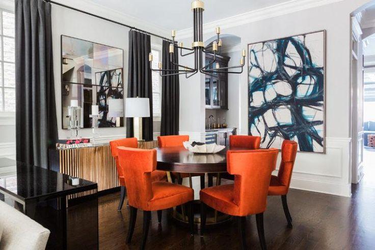 Der Essbereich ist kühn und glam, da ist ein großes Kunstwerk, ein Spiegel, ein Messing und schwarzer Kronleuchter und super bunte verbrannte Orangenstühle