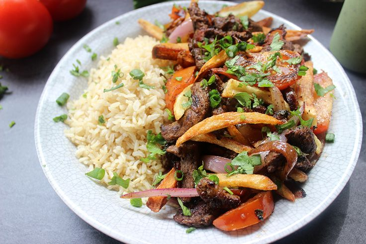El Pollo Inka's most popular entree, Lomo Saltado, is sliced steak, onions, tomatoes, fries and cilantro topped with spicy green aji sauce and brown rice.