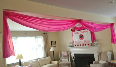 Drape it: 1. Use small Command hooks at corners. 2. Gather plastic tablecloth and wrap with twist tie. 3. Hook twist tie loop onto Command hook. 4. Add tulle to completely cover the Command hook.