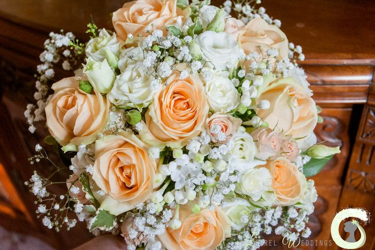 Pretty bridal bouquet of peach and ivory roses with gypsophila