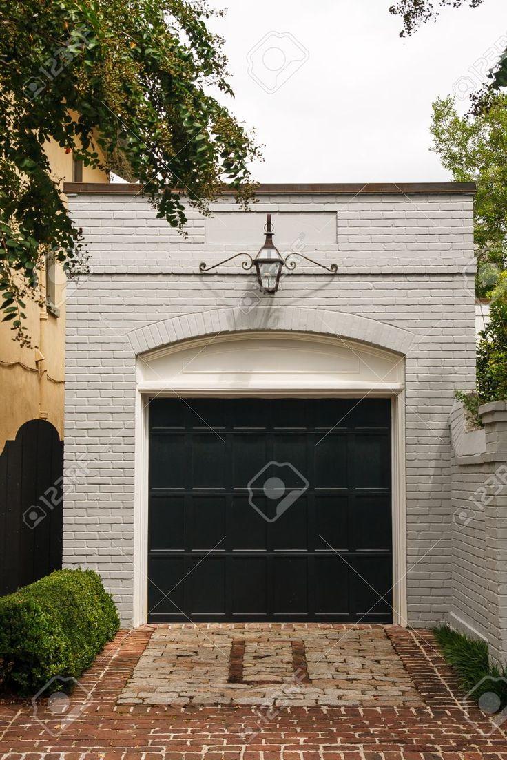 Een oude witte bakstenen vrijstaande garage met een zwarte houten deur boven een bakstenen oprit