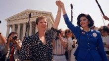 """In this 1989 photo, Norma McCorvey, """"Jane Roe"""" in the 1973 Roe v. Wade Supreme Court case, left, and her attorney, Gloria Allred, hold hands as they leave the Supreme Court building in Washington after sitting in while the court listened to arguments in a Missouri abortion case."""