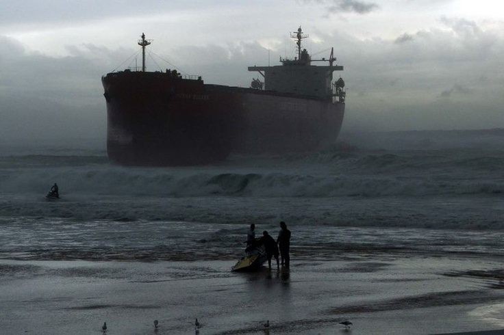Local jet ski riders on Nobbys Beach, Newcastle, are dwarfed by the MV Pasha Bulker after it ran aground there on June 8, 2007. Richard Brown via ABC