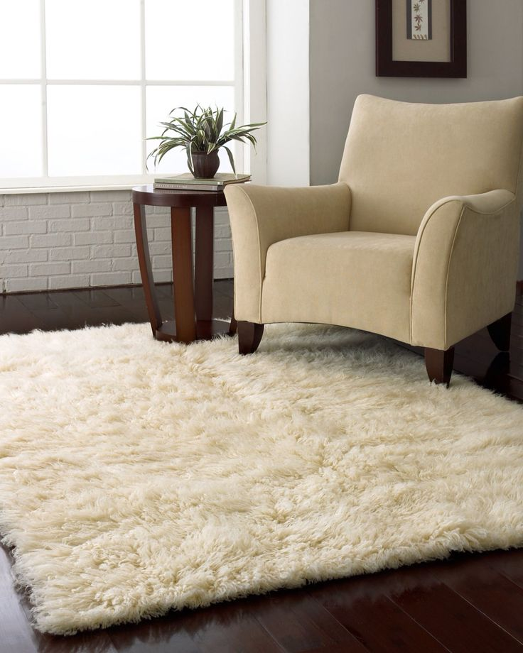 White fluffy rug for under the bed on the hardwood floors