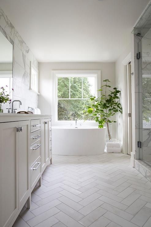 Welcoming white bathroom is fitted with honed white marble herringbone floor tiles fixed framing a white dual washstand accented with polished nickel hardware and a white quartz countertop finished with polished nickel faucets mounted beneath frameless vanity mirrors hung from a marble subway tiled wall.
