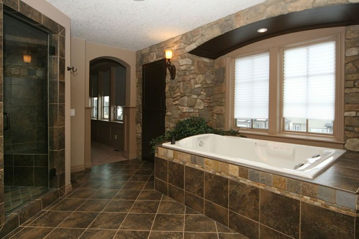 Dark stone tiled bathroom with stone accent walls - feels like a cave | Calgary