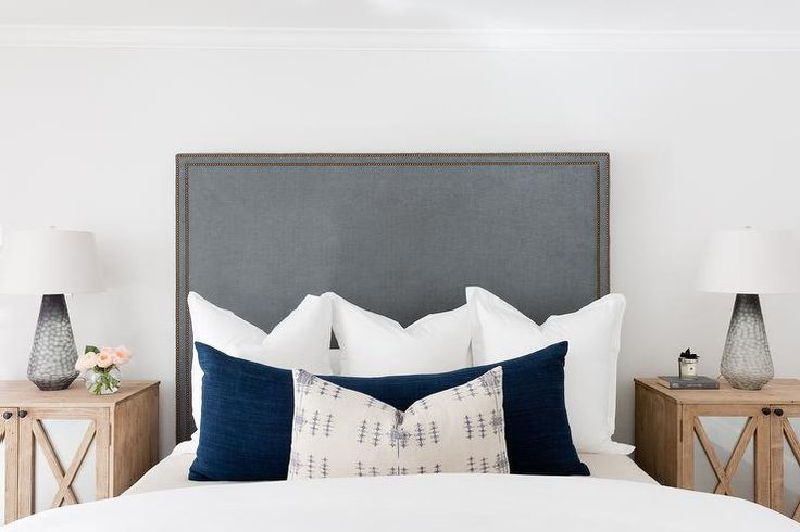 Flanked by x-front nightstands lit by white and gray lamps, a tall gray velvet headboard accented with a brass trim supports a bed dressed in white hotel bedding topped with white shams layered behind a long blue velvet lumbar pillow.