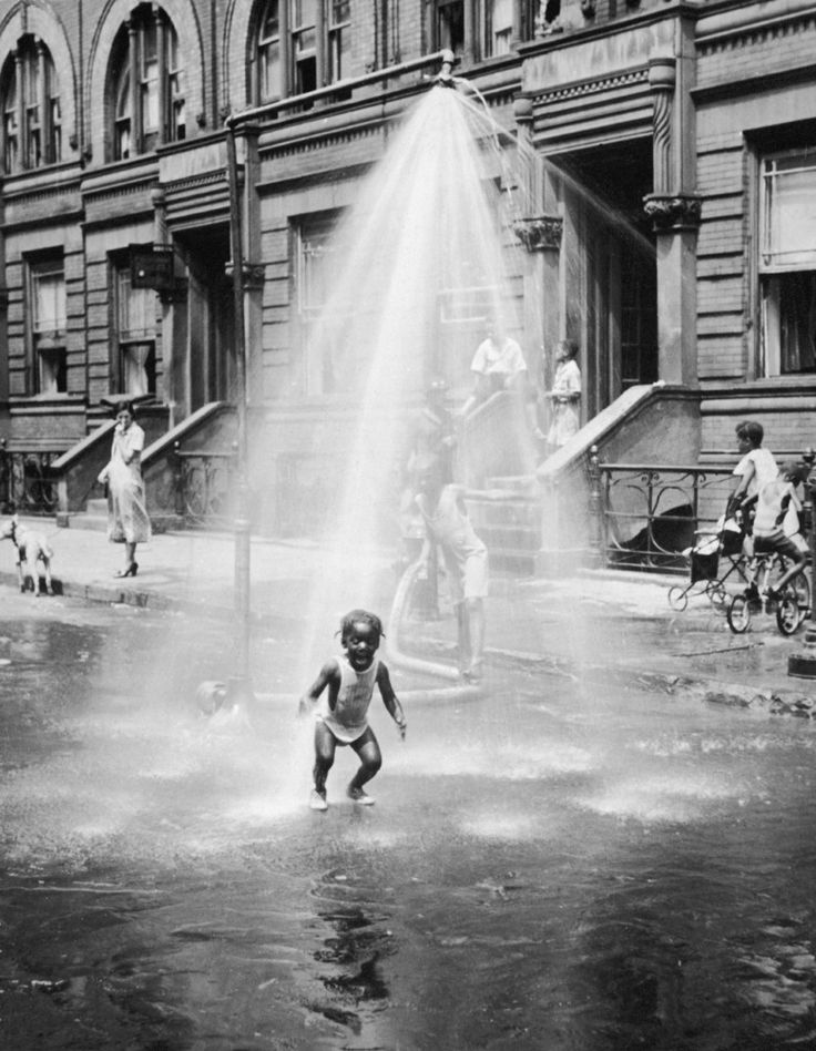 23 Vintage Photos That Show What Summer Fun Looked Like Before The Internet --- A young girl plays under the spraying water of a special shower constructed in the street and connected to a fire hydrant on a hot Summer's day as adults and other children look on, July 19, 1937. (Photo by Charles Fenno Jacobs/The LIFE Images Collection/Getty Images)