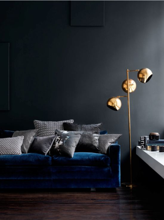 Blue velvet sofa and brass lamp