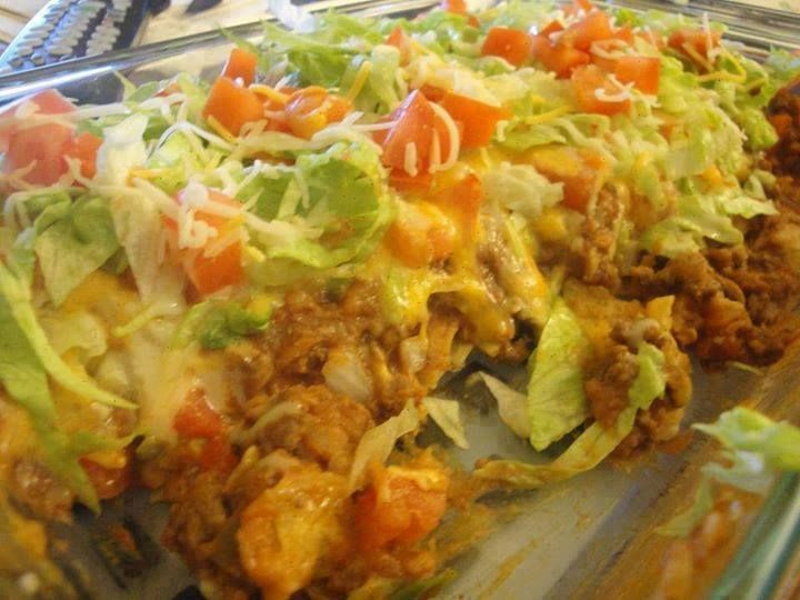 INGREDIENTS:  7oz. bag Nacho Cheese Doritos, crushed  1 lb lean or extra lean ground beef  1/2 cup diced onion (optional)  1 pkg. taco seasoning, mixed according to directions  1 (8 oz.) pkg. shredded Cheddar cheese  1 (8 oz.) pkg. shredded Mozzarella