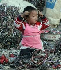 A baby girl sits in a pile of wires waiting for her parents to come back from searching through the garbage. Corporations take advantage of the poverty in these countries and dump their electronic devices. Children are being raised in a dump while in the western world, people upgrade their phone because it is slightly out of date.