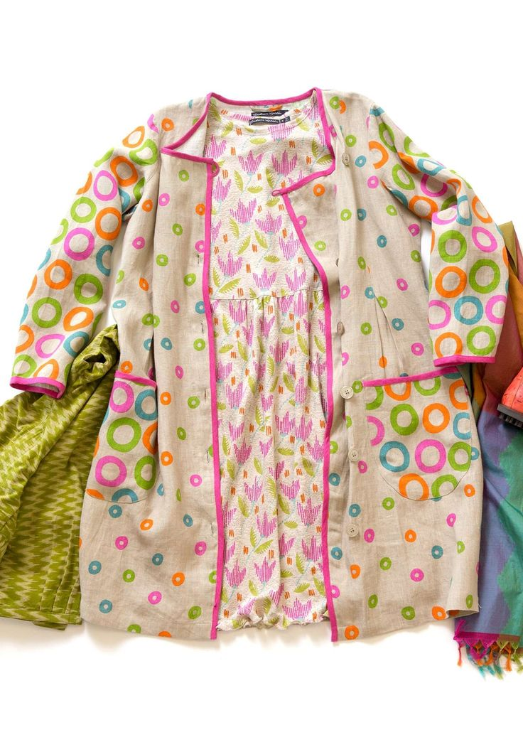 "An indoor coat or a dress with diagonally shaped fastening and two wonderful patch pockets. A pure linen fabric adorned with the playful ""Circulo"" print and pretty braid trim."