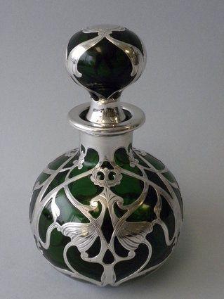 An Antique American Green Glass Sterling Silver Overlay Perfume Bottle of an Art Nouveau Design. $3,250