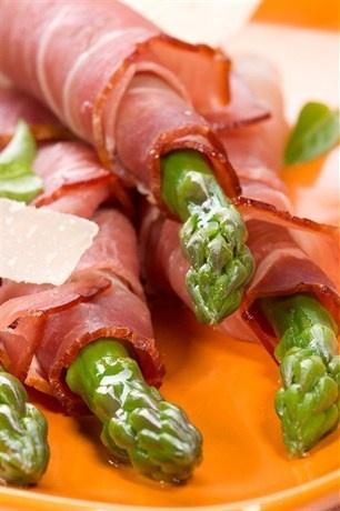 Спаржа, завернутая в ветчину серрано, с листьями салата, миндалем и виноградом