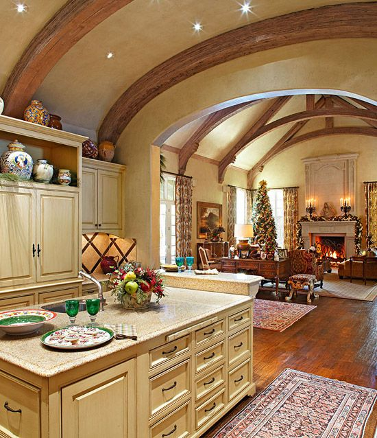 Because large-scale furnishings and blocky granite-topped cabinets provide needed visual weight to the rooms, and are in keeping with the French country look of the house. A two-level island allows for seating at one end, so guests and family members can chat with the cook. The raised island also shields the great room's views of dirty dishes.
