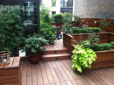 Custom-built NYC roof garden features beautifully stained ipe deck, red ceramic planter and planter box with plantings of evergreen plants near Gramercy Park. We Plantings include bamboo, hydrangeas, evergreens, and red Japanese maples. We have installed roof top drip irrigation systems and landscape lights for this roof top garden. Read more about our projects on my blog http://www.newyorkplantings.com/. New York Plantings Garden Designers and Landscape contracting 432 E 14st  New York, NY…
