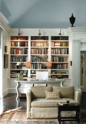 Home library with white bookshelves, sconce lighting, desk - and blue  ceiling