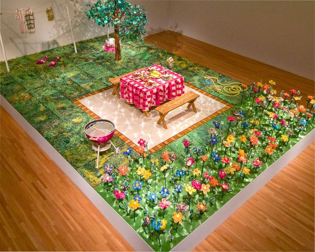"""Back Yard =- Bead artist Liza Lou created """"Kitchen"""" and """"Back Yard,"""" two full-scale replicas that are entirely covered in millions of sparkling glass beads. Lou began work on """"Kitchen"""" in 1991 and completed it five years later. Each bead covering the tablecloth, a bag of potato chips, and other objects in the room was painstakingly hand-glued with a set of tweezers. """"Back Yard"""" was created between 1996 and 1999 and features sparkling glass-beaded trees, grass, and even a lawnmower and grill."""