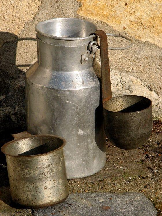 Bidon à lait et mesures en fer blanc. Tous les soirs d'été, le lait frais à la ferme. Jamais pu en boire!