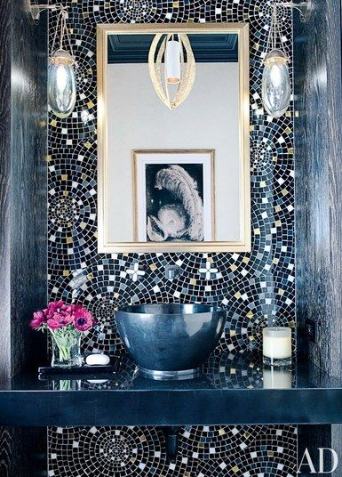 A custom-made glass-tile wall treatment created by designer Jamie Drake and Cheryl Hazan Mosaic animates a Manhattan powder room; the hanging light is by Porta Romana, the sconces are by Jonathan Browning Studios, and the sink fittings are by Drake for THG | archdigest.com