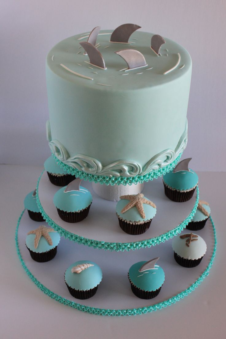 Shark themed baby shower cake with matching cupcakes.  Cupcakes have shark fins, star fish, driftwood and sea shells all in varying shades of teal.