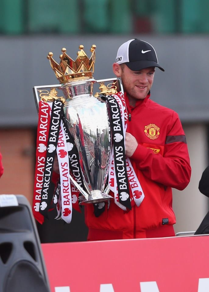 Wayne Rooney is Posing for pictures with the Premier League trophy