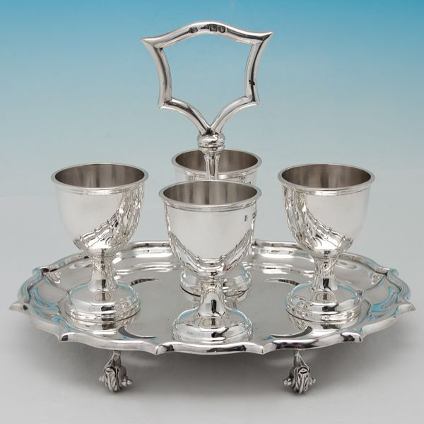 Hallmarked in London, 1898 by Turner Bradbury, this handsome, Victorian, Antique, Sterling Silver Egg Cruet, featured four egg cups with reed borders, a shaped stand on four scroll feet, and space for four egg spoons. The egg cruet measures 5.75 inches (14.5cm) tall, by 7.5 inches (19cm) wide, by 5.5 inches (14cm) deep, and weighs 18.1 troy ounces.