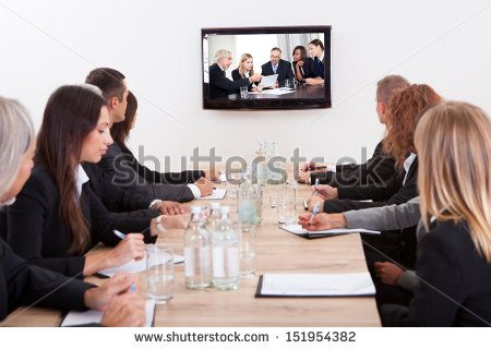 Businesspeople Sitting At Conference Table Looking At Flat Screen Display - stock photo