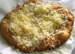 Langos: Plain flour – 2 cups, Yeast – 1 packet, Salt – to taste Mix the yeast, salt and flour together and make dough with warm water. Let it set for 30 minutes, then roll the dough like roti and cut in the middle one after the other and fry in a deep oil and put cheese garlic on top and serve hot.