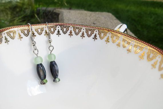 These simple glass green and brown drop earrings are sure to bring you down to earth with their natural colors. From the top, the earring holds a round, green, artificial sea-glass bead, followed by a brown glass bead that resembles the inside of a shell, and is finished with a green glass crystal-cut bead. $10.50
