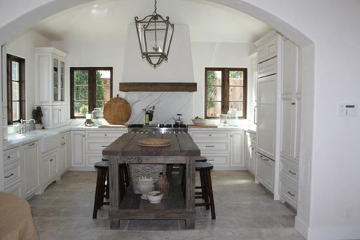 European kitchen boasts a French iron and glass lantern illuminating a freestanding reclaimed wood island with shelf lined with rustic round counter stools.