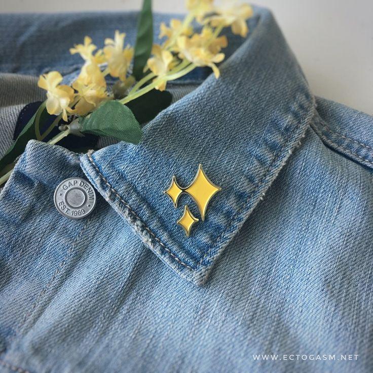 sparkle emoji enamel pin on a lapel.