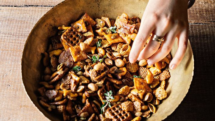 Maple syrup is teamed with cayenne pepper, vinegar, and fresh thyme to flavor this addictive party-ready blend of peanuts, pepitas, crackers, pretzels, and cereal.
