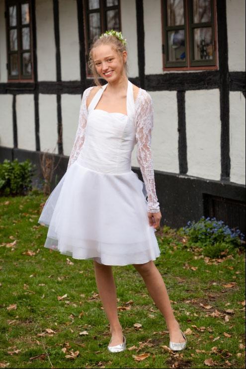 Sigrids kjole er enkelt og klassisk. Den består af en corsage med halterneck og skørt med fyld fra tyl. Modellen er lavet ud fra en prøvemodel fra Stof 2000.  Den er syet i Thai silke og brude tyl med en blonde bolero til.
